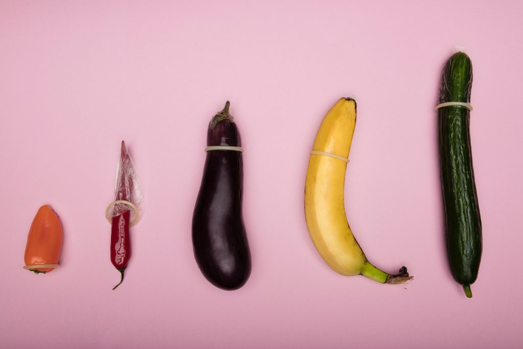 A bell pepper, a chili pepper, an eggplant, a banana, and a cucumber each wearing a condom.