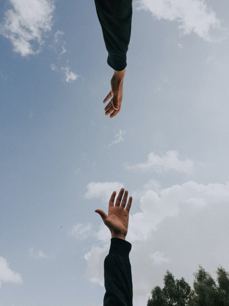 Two hands reaching towards the sky.