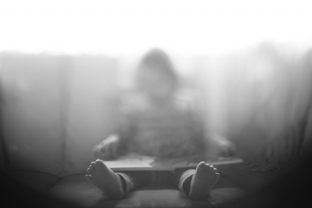 A child sitting down on a couch; there is a blurred filter over the child.