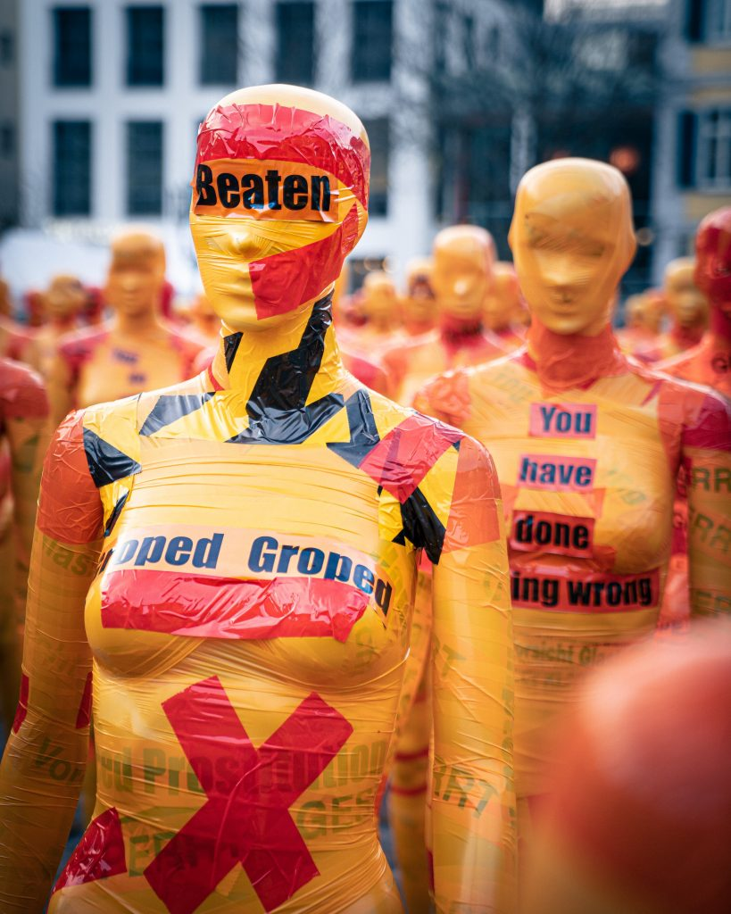 """Yellow mannequins with patches of red duct tape on body and head. The words """"Groped,"""" """"Beaten,"""" and """"You have done nothing wrong"""" are written on the mannequins' eyes and breasts."""
