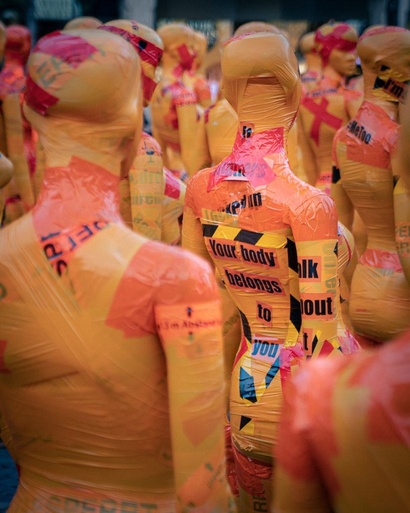 """Yellow mannequins with the words written """"your body belongs to you"""" on their back."""