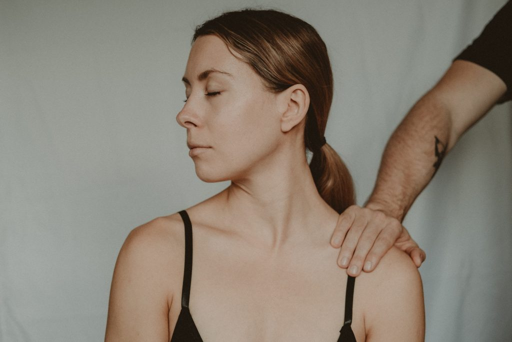 A person's hand is on a woman's shoulder. The woman has her eyes closed and is facing away from the person.