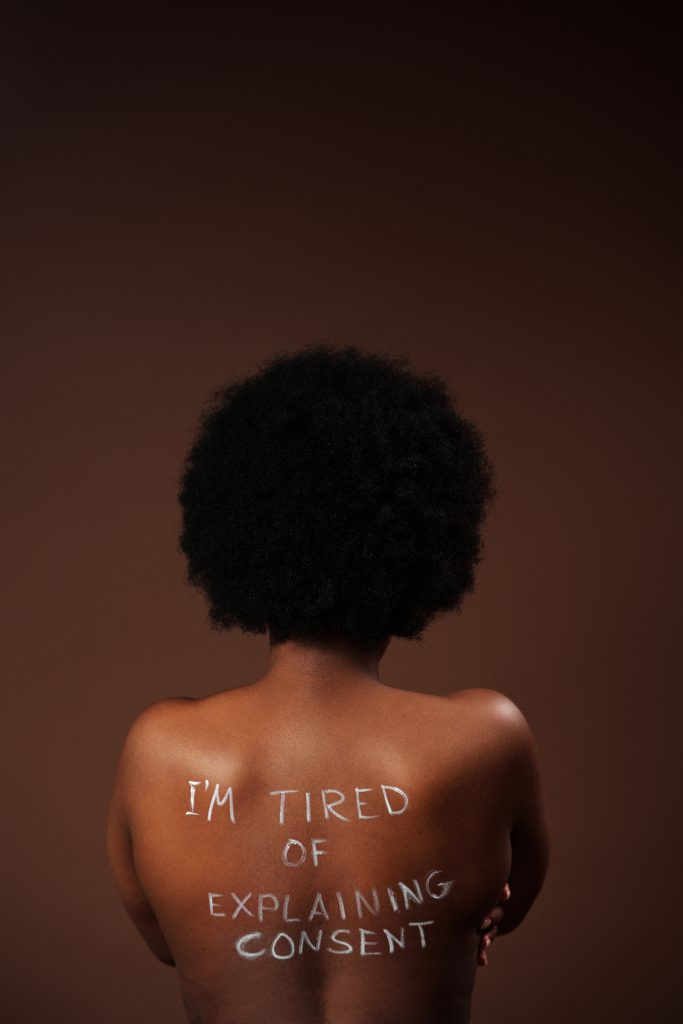 "A topless person with ""I'm tired of explaining consent"" written on their back."