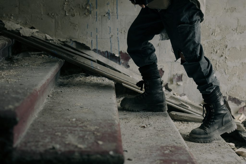 A person walking up stairs. The person is wearing boots and the wall behind them is torn apart.