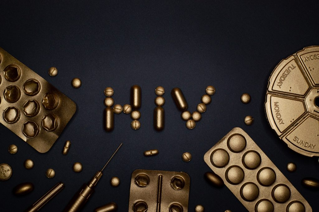 """""""HIV"""" spelled out with pills covered in gold."""