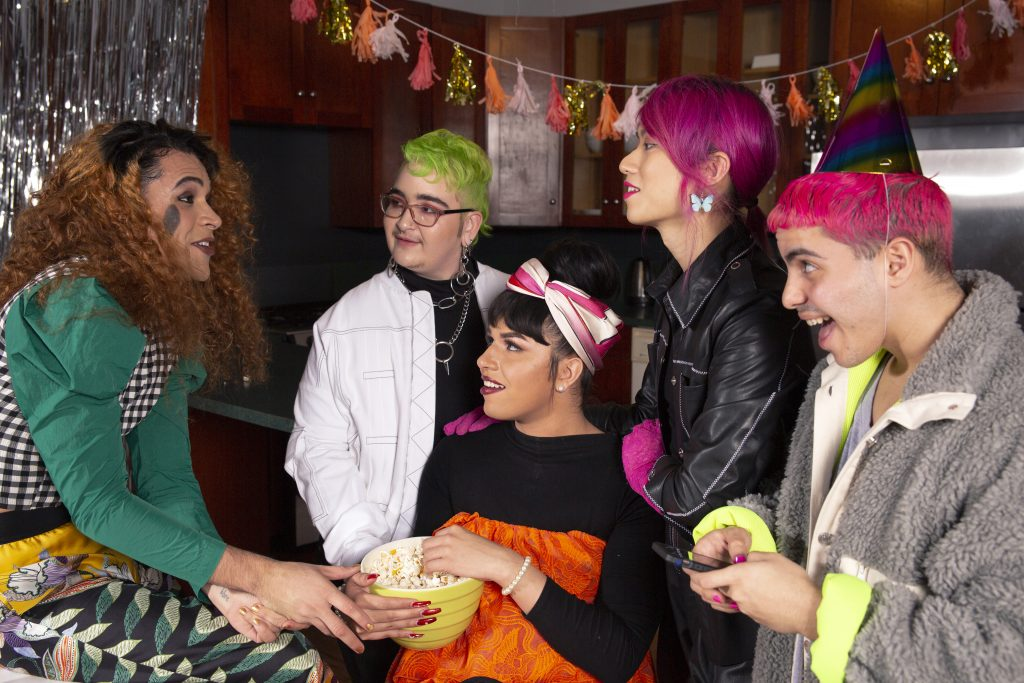 A group of friends gathered together. They have different colored hair; one person has green hair, two have pink hair, and the other two have brown hair.