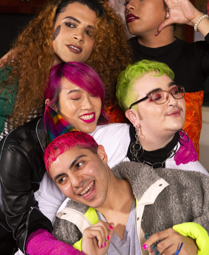 A group of five people hugging each other. They have different colored hair and are smiling.