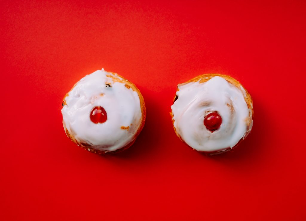 Two cupcakes with white frosting and a cherry on the middle of each cupcake. The cupcakes resemble breasts.