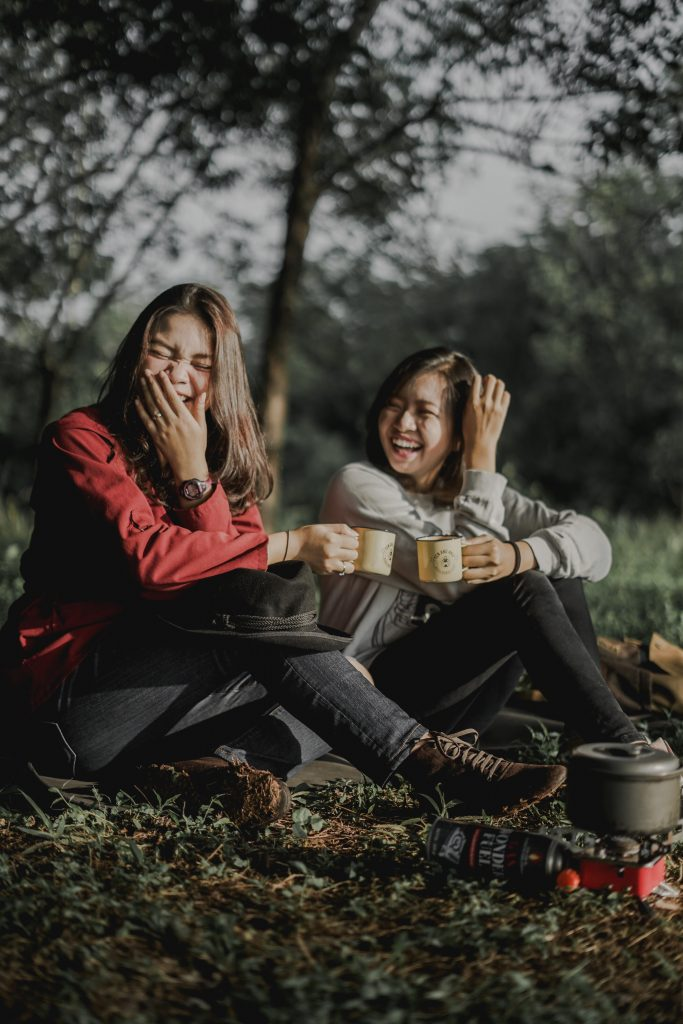 A couple sitting on grass, in the woods, and laughing. They are each holding a mug.