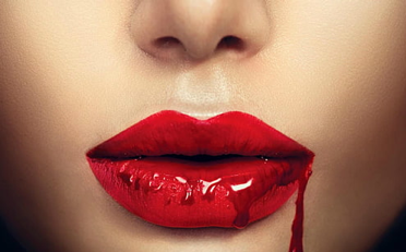 Person's red lips covered in blood.