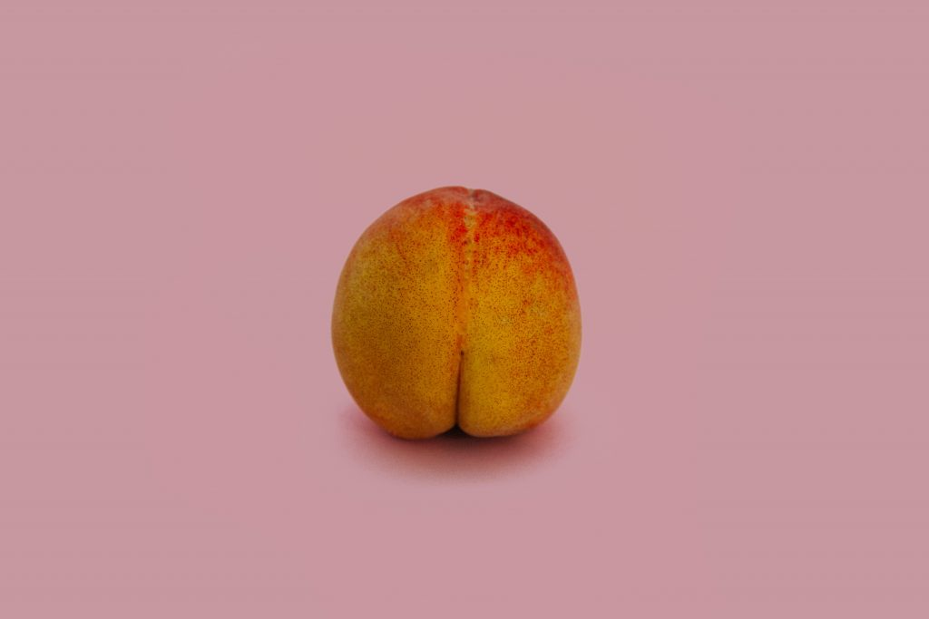 a peach in front of a pink background