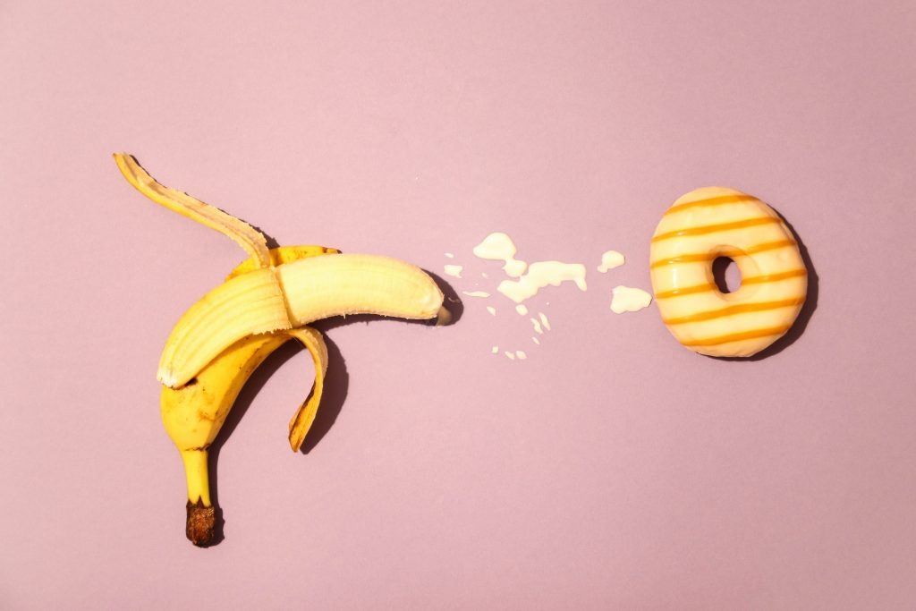 A banana squirting a milky substance next to a donut.