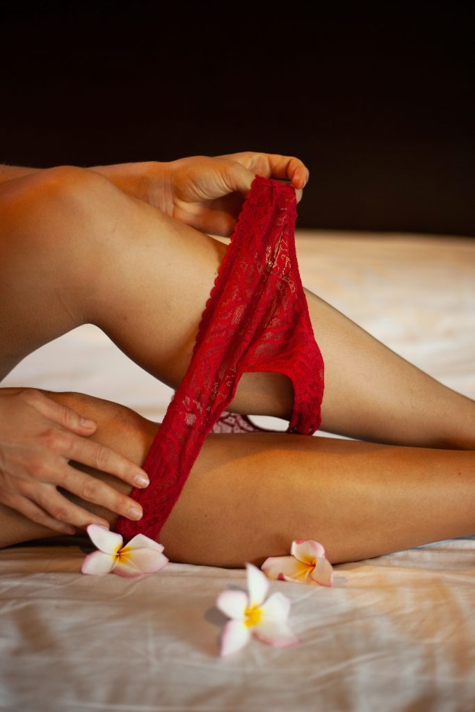A person removing red underwear from legs.