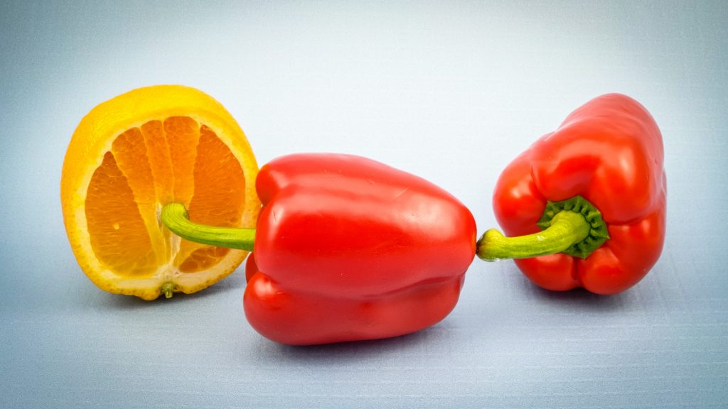 A bell pepper's stem touching another bell pepper. The second bell pepper's stem is poking the inside of an orange.
