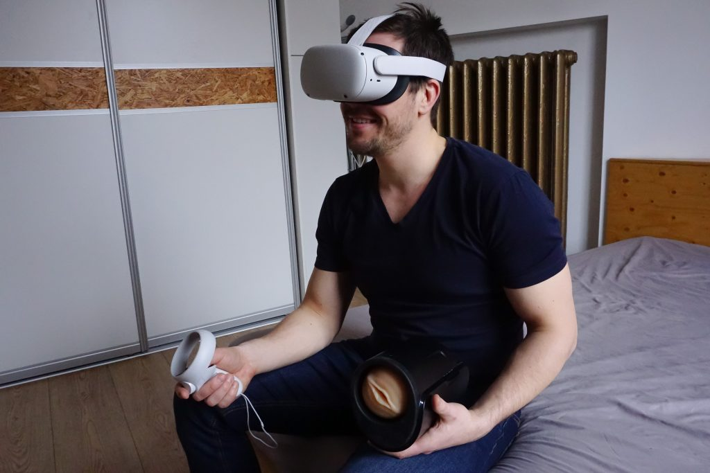 A person wearing a virtual reality headset. The person is holding a masturbation sleeve and another with device with a button.