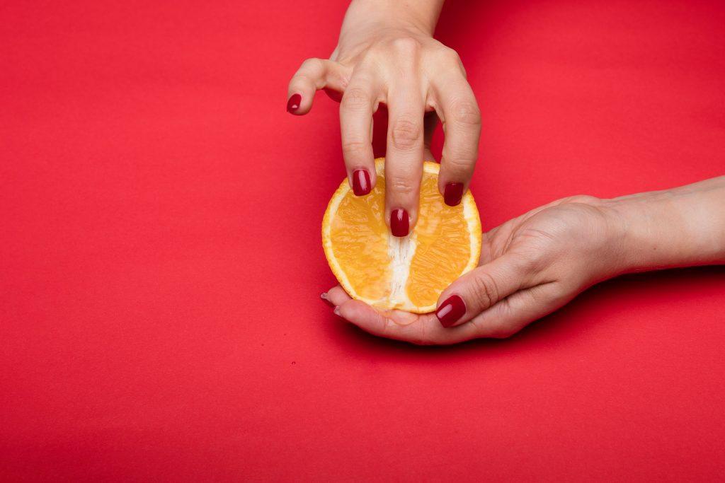 A person fingering an orange that resembles a vagina.