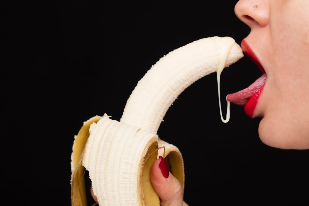 A person sticking their tounge out while holding a banana that is dripping a milky substance.