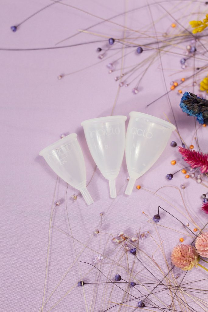 Three menstrual cups next to flowers.