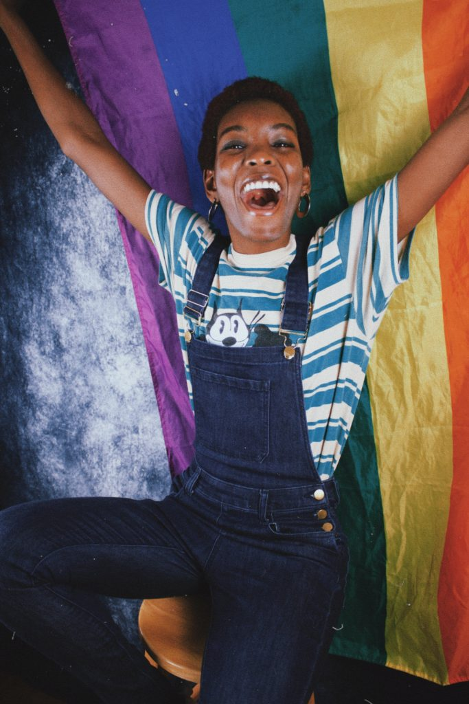 A person standing in front of an LGBTQ flag. The person has a big smile on their face.