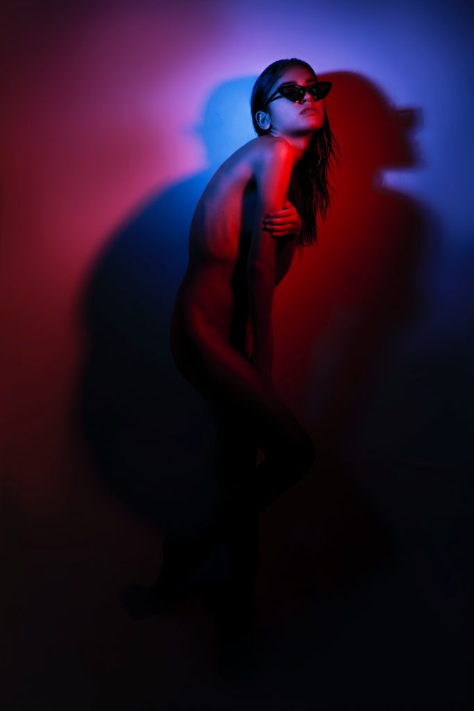 A naked person wearing sunglasses and posing in the dark.