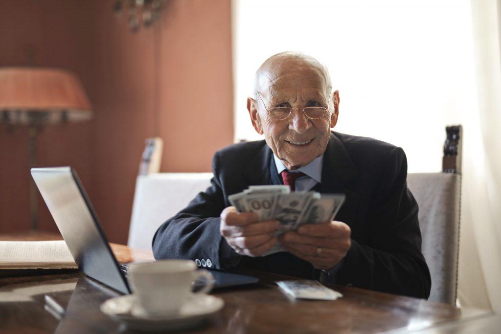 An older bald man smiling. He is holding multiple hundred dollar bills.