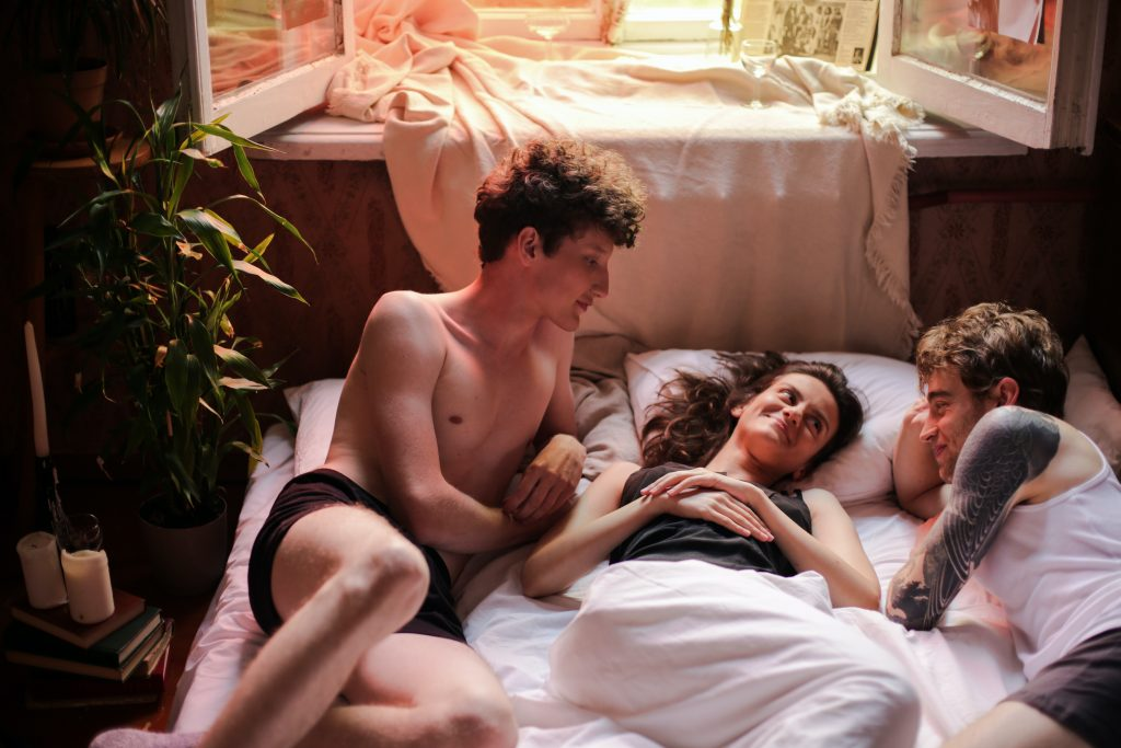 Three persons laying on a bed. They are all smiling at each other.