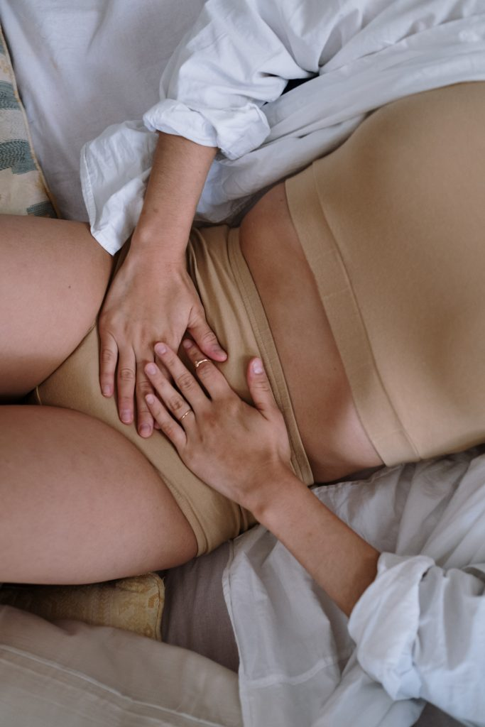 A person dressed in a tan cropped top and tan underwear. The person is holding over their abdomen.