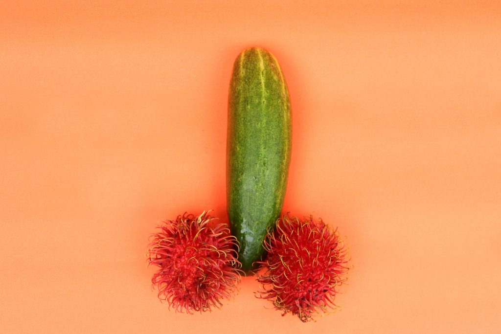 A cucumber in the middle of two rambutan fruits. The cucumber resemble a penis and the rambutans resemble testicles.