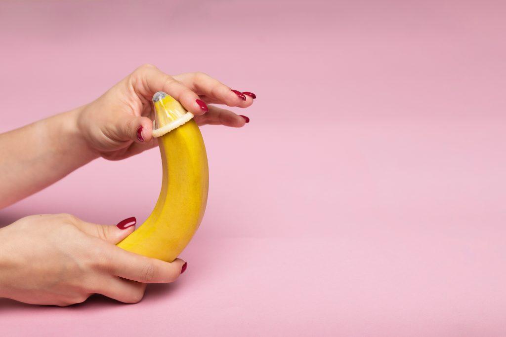 A person applying a condom on a banana.