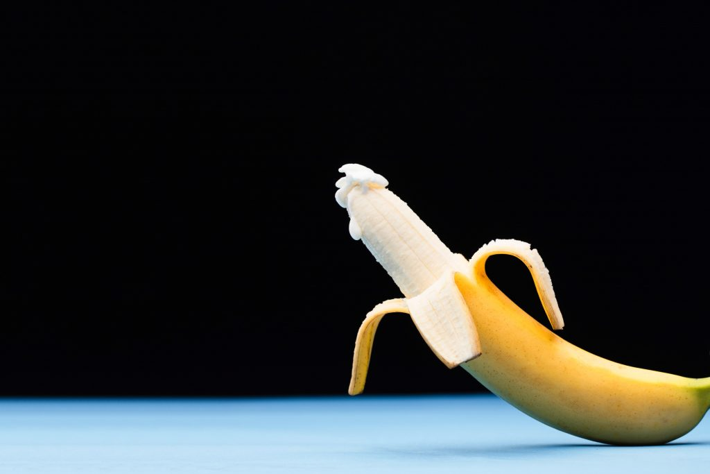 A half peeled banana with a thick substance on the tip.