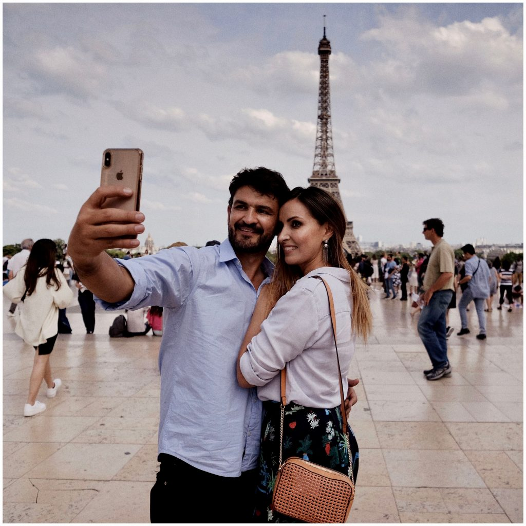 A couple taking a selfie in front of the Eiffel tower.
