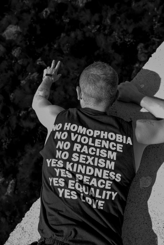 """A person wearing a shirt that says """"NO HOMOPHOBIA, NO VIOLENCE, NO RACISM, NO SEXISM, YES KINDNESS, YES PEACE, YES EQUALITY, YES LOVE."""""""