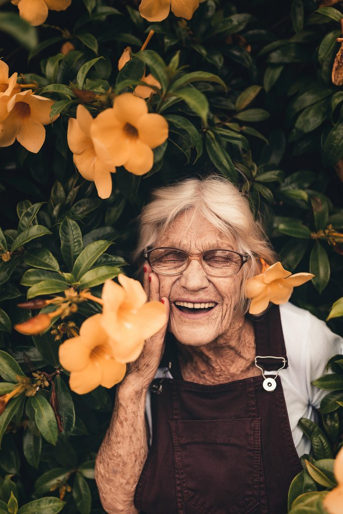 An older woman smiling, with her eyes closed. She is in front of green leaves and orange flowers.