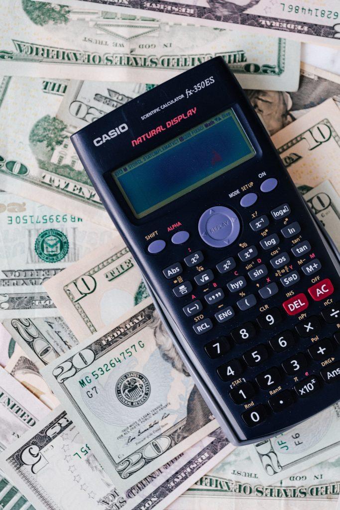 A calculator on top of U.S. dollar bills.