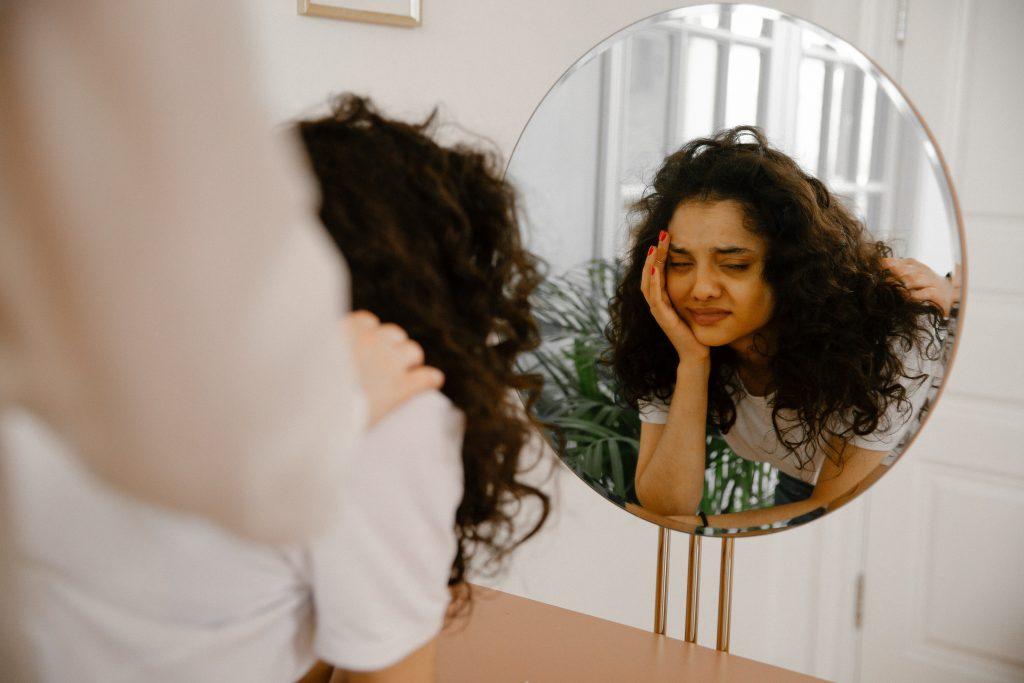 A person on a circular mirror. The person's face shows distress.