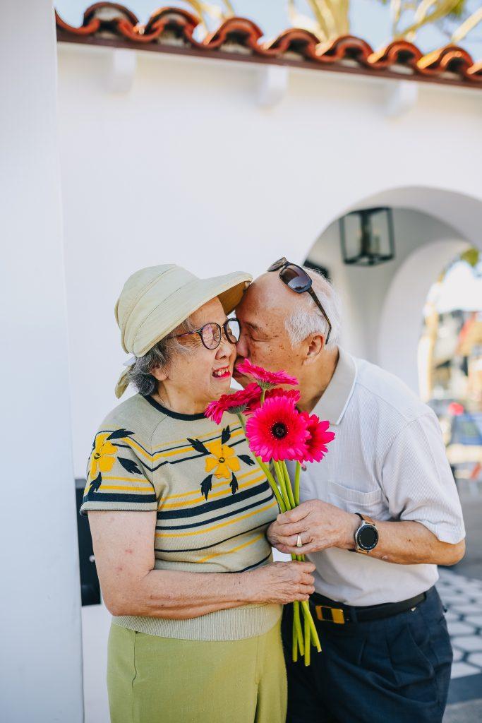 An older man kissing an older woman on the cheek.