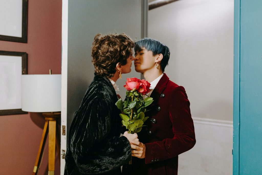 A couple nearly kissing; their faces are in close proximity. They are holding roses.