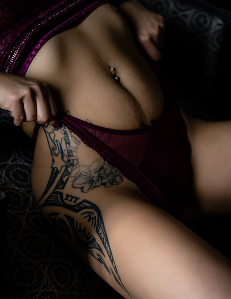 A tattooed person lifting up their maroon panties.