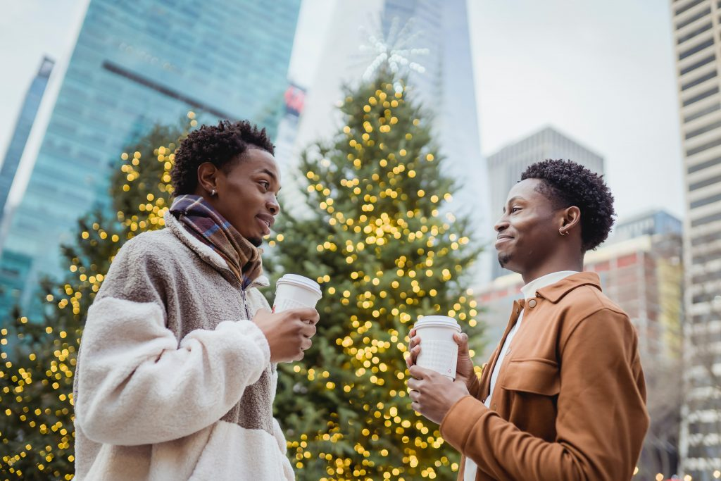Two men holding coffee cups, facing each other. There are Christmas trees behind them.