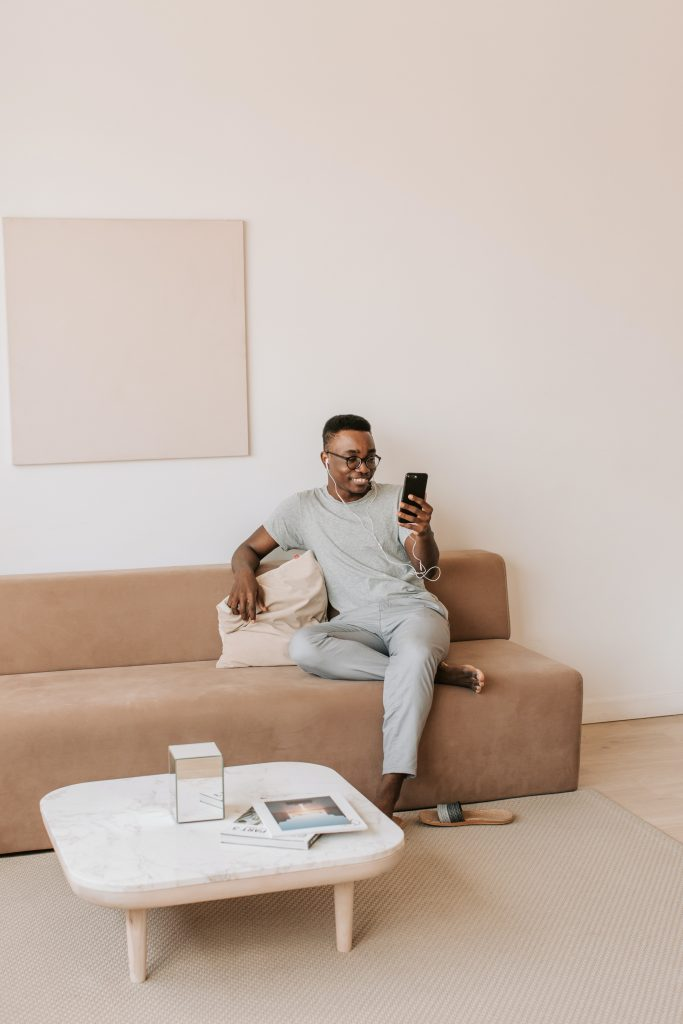 A person sitting on a couch. The person is smiling at their phone and wearing earphones.