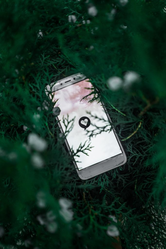 A phone with a white screen and a black heart on the middle of the screen. The phone is on top of grass.