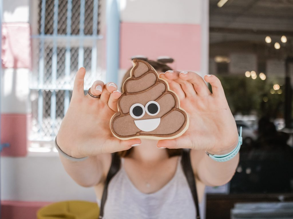 A person holding a cookie that is shaped like a poop with a smiley face.