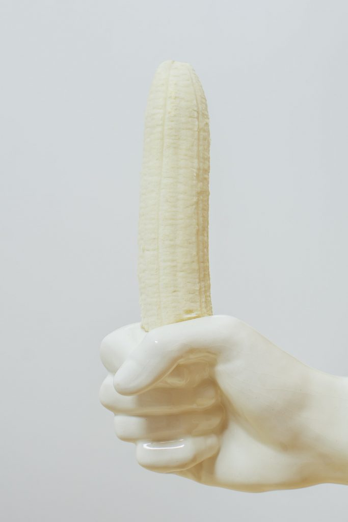 A white mannequin hand holding a long banana.
