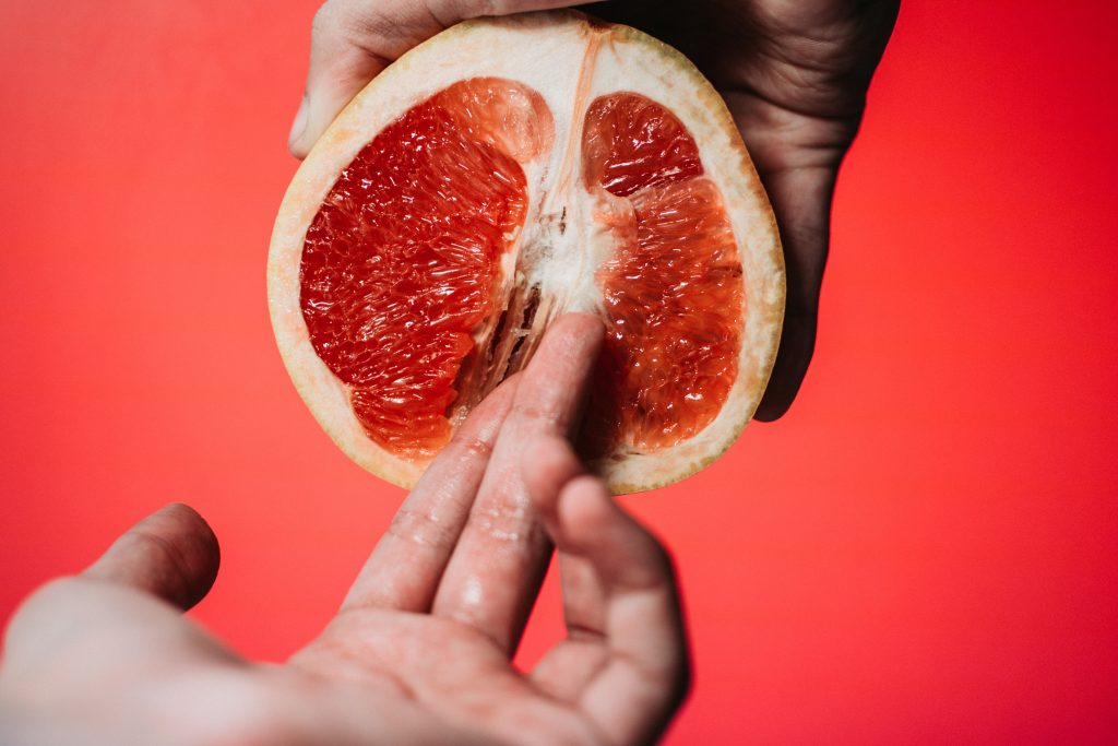 A hand holding a grapefruit, while another hand touches the grapefruit with two fingers.