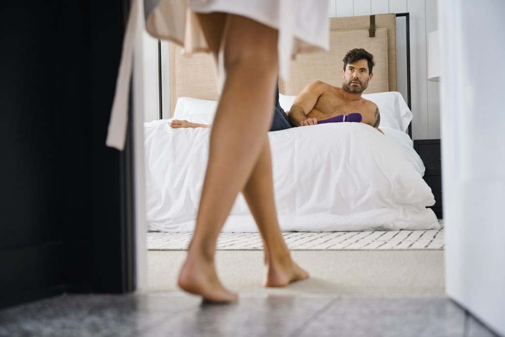 A man holding a vibrator on a bed. A person's legs are shown walking toward the man on the bed.
